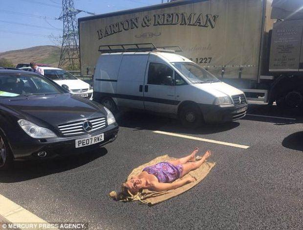 KËTË NUK E KISHIT PARË/ U bllokua trafiku për 3 orë, gruaja vendos të marrë rreze dielli në asfalt (FOTO)